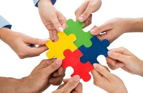 Mains avec 4 morceaux de puzzle en couleurs
